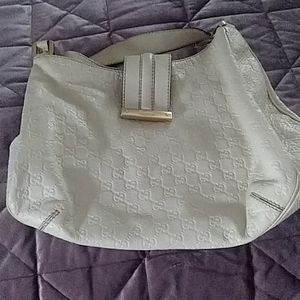 This is a cream-colored authentic Gucci pocketbook